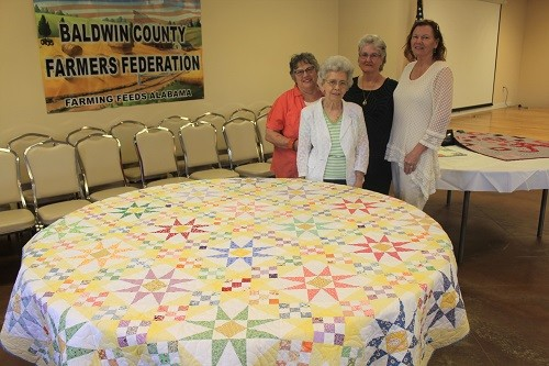 Pictured with Bonnie Savell's winning entry in the machine stitched cotton quilt category are, from left, Barbara Krob, Christmas tree skirt; Bonnie Savell; Pam Madden, hand-stitched cotton quilt; and Kathy Byrd, machine stitched baby quilt.