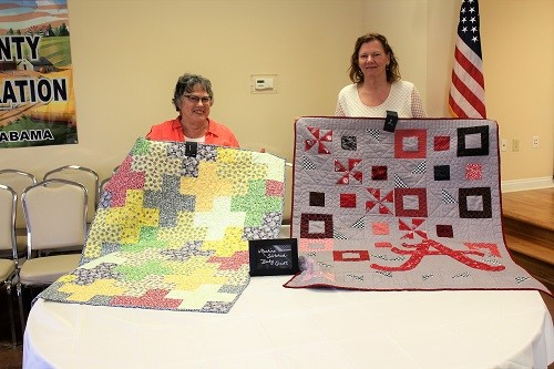 Barbara Krob and Kathy Byrd with their machine stitched baby quilts.
