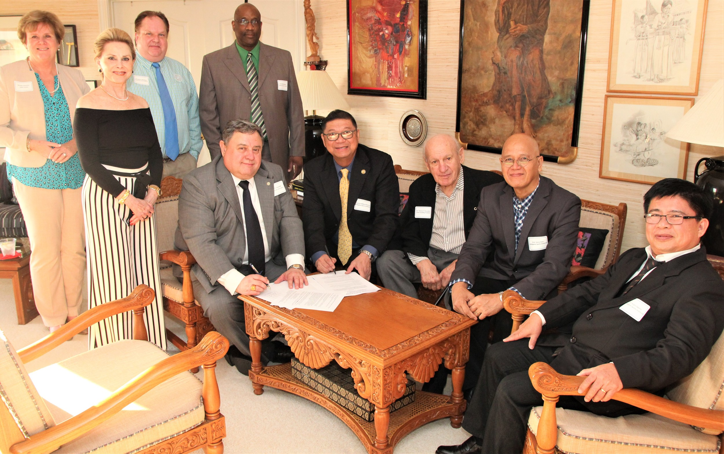 "United States Sports Academy President and CEO Dr. T.J. Rosandich, seated at left, signed an agreement with Philippine Sports Commission (PSC) Chair William ""Butch"" Ramirez, seated second from left, to help enhance that country's national sport programs at all levels. Also shown are, standing from left: Academy Trustees Darrelyn Dunmore and Susan McCollough, Academy Chair of Recreation Management Dr. Rodney Blackman and Interim Dean of Academic Affairs and Director of Doctoral Studies Dr. Fred Cromartie. Seated from left are Rosandich, Ramirez, Academy Founding President Dr. Thomas P. Rosandich, Philippine Sports Institute deputy training director Henry Daut and PSC Director of Operations Sergio Opena."