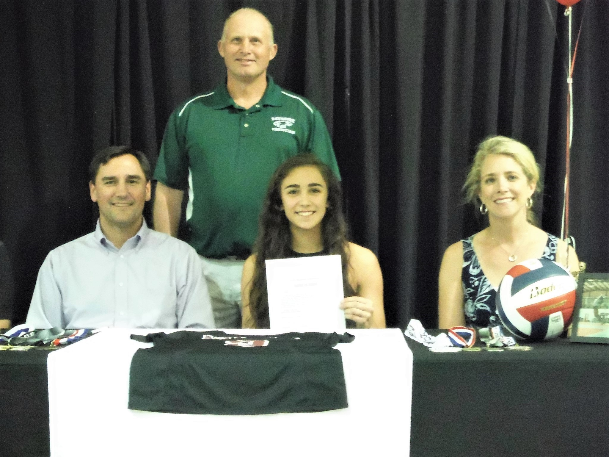 Ashley Conrad, seated center, between her parents Chris and Natalie with BCS volleyball coach Dave Omtvedt.
