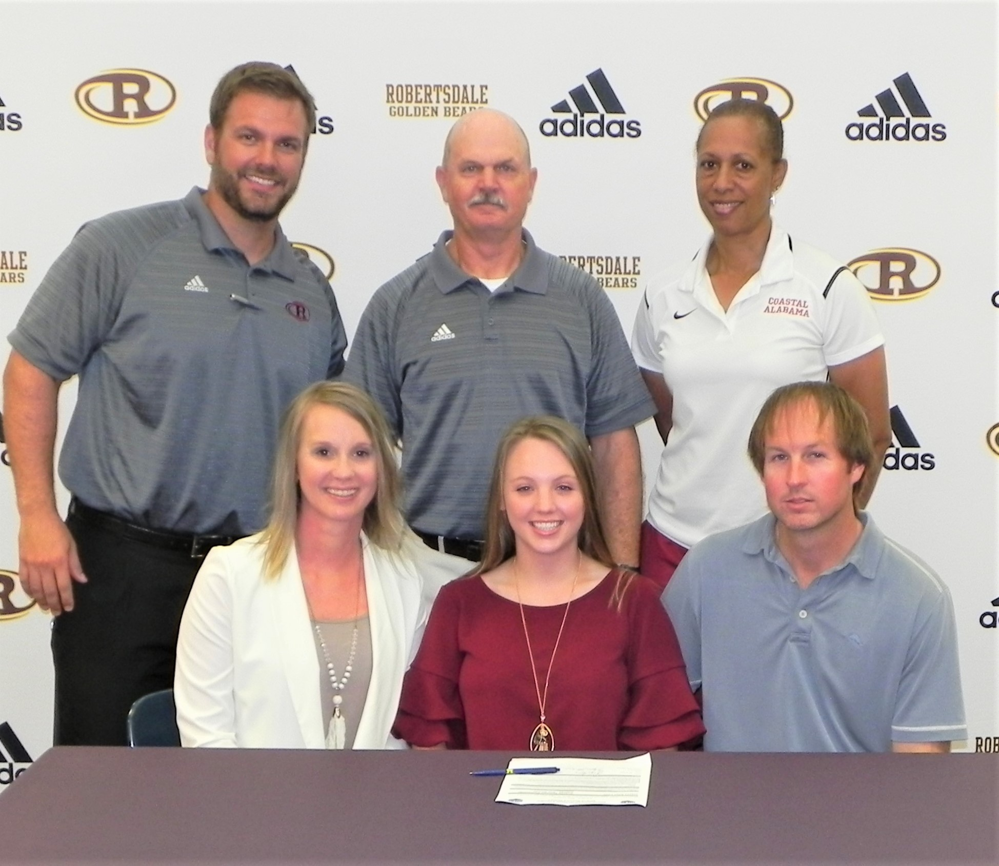 Robertsdale's Chloee Lynn, seated, flanked by parents Tonya and Steve Lynn, recently signed a tennis scholarship with Coastal Alabama Community College South in Bay Minette. Standing are, from left, RHS Athletic Director Chase Smith, Lady Bears Tennis Coach Wayne Davis and CACC tennis coach Dr. Ritchie Dulaney.