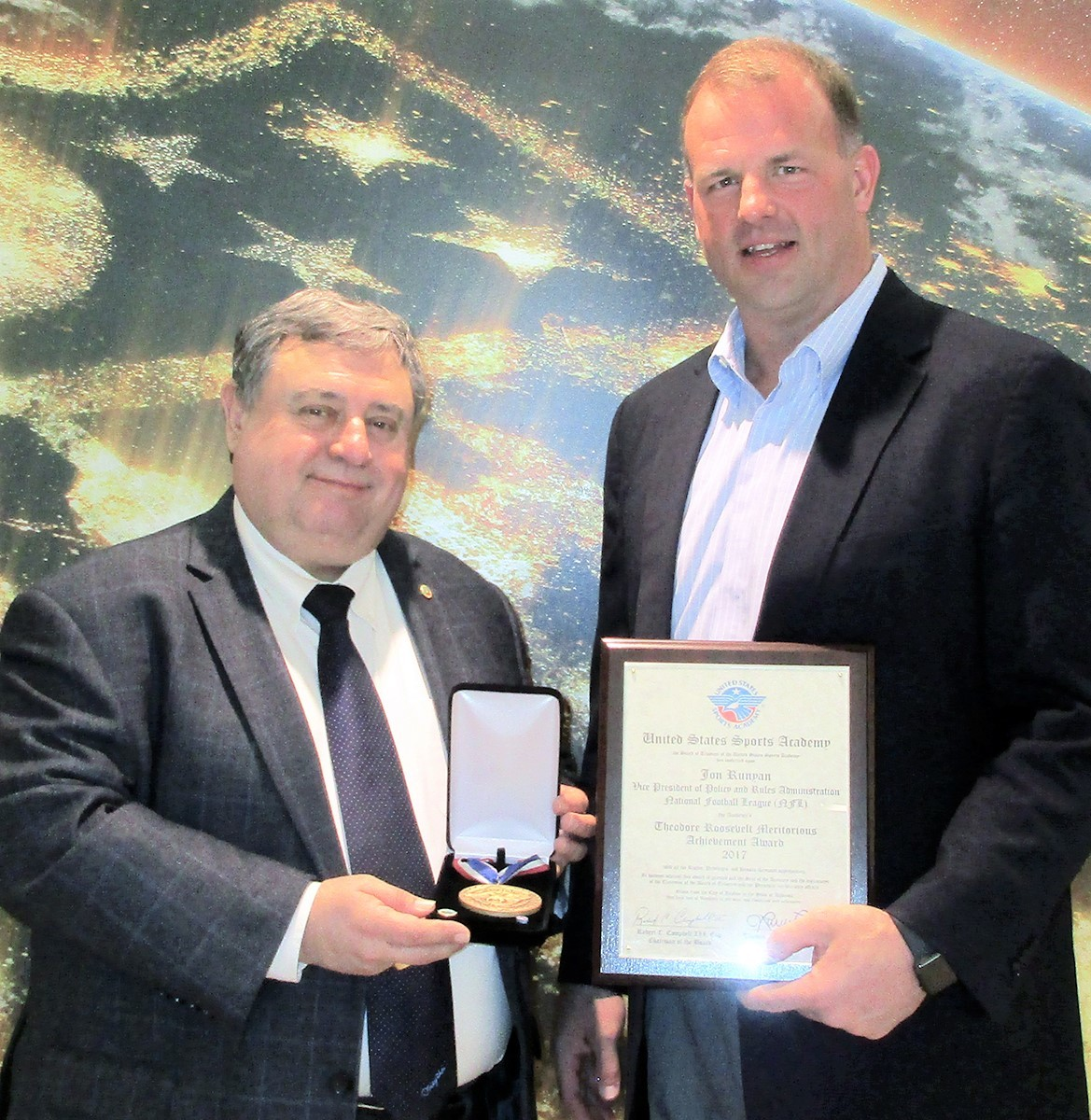 Former National Football League player and U.S. Congressman and current NFL Vice President of Football Operations Jon Runyan, right, recently was presented the United States Sports Academy's 2017 Theodore Roosevelt Meritorious Achievement Award by Academy President and CEO Dr. T.J. Rosandich at the NFL offices in New York City.