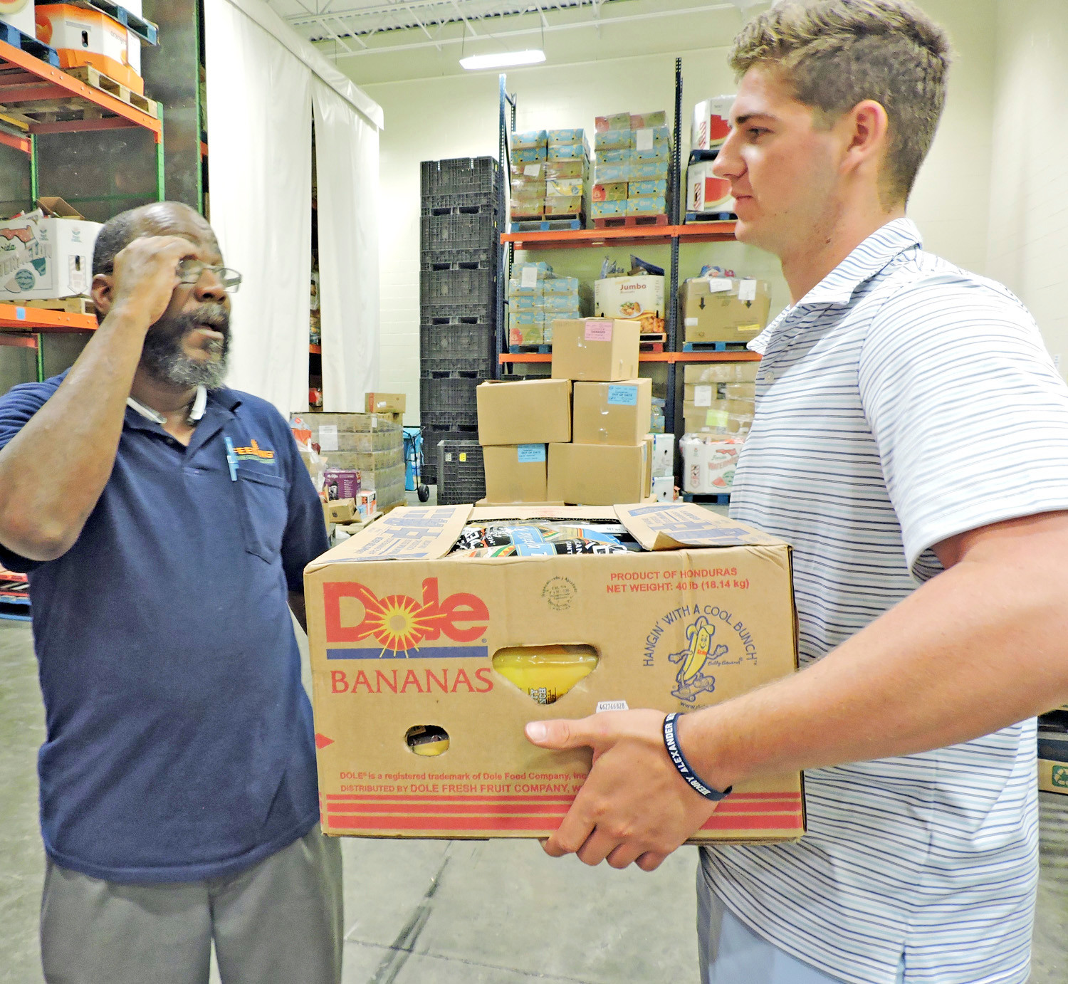 Volunteer Sam Koby of Bayside Academy, right, gets instructions from Ron Henderson, the reclamation coordinator for Feeding the Gulf Coast, on unloading an incoming box of groceries that will be distributed to the needy in Mobile.