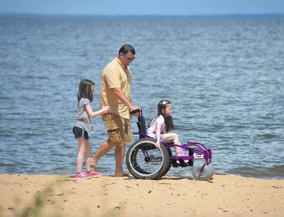 Fairhope's Katelynn Horne gets to enjoy her new beach wheelchair, donated to her by Tyler Thompson of Opelika-based Angels of Alabama organization.