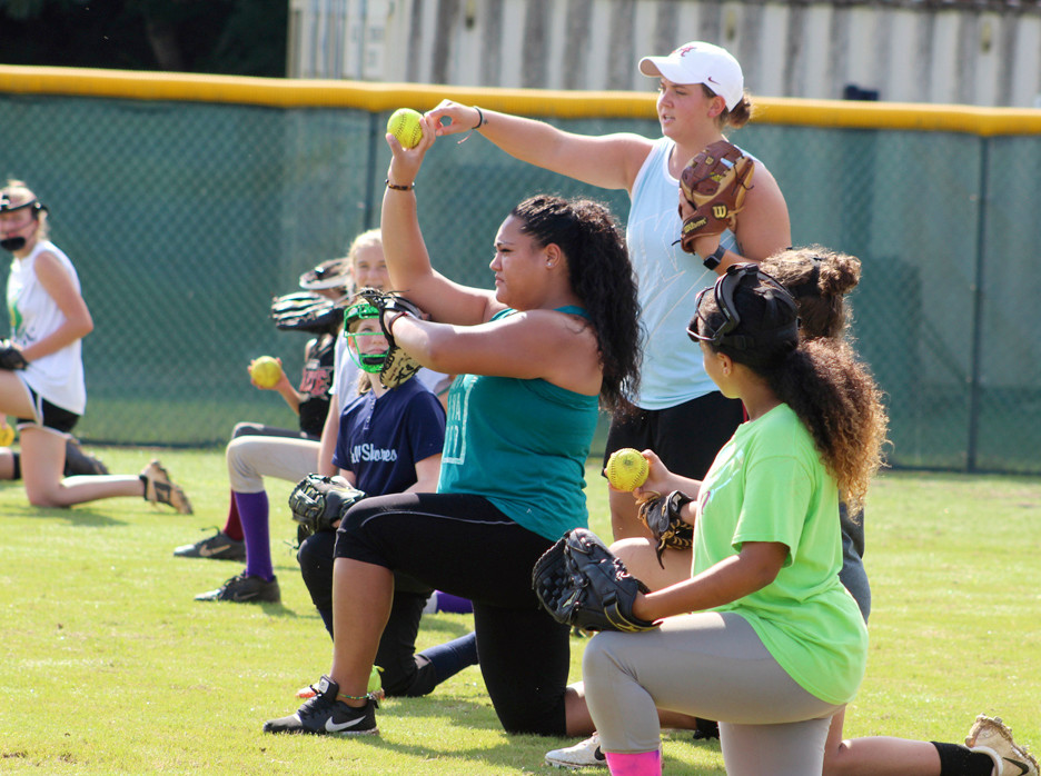 Peyton Grantham, standing, and Leona Lafaele talk about gripping and throwing the ball with players.
