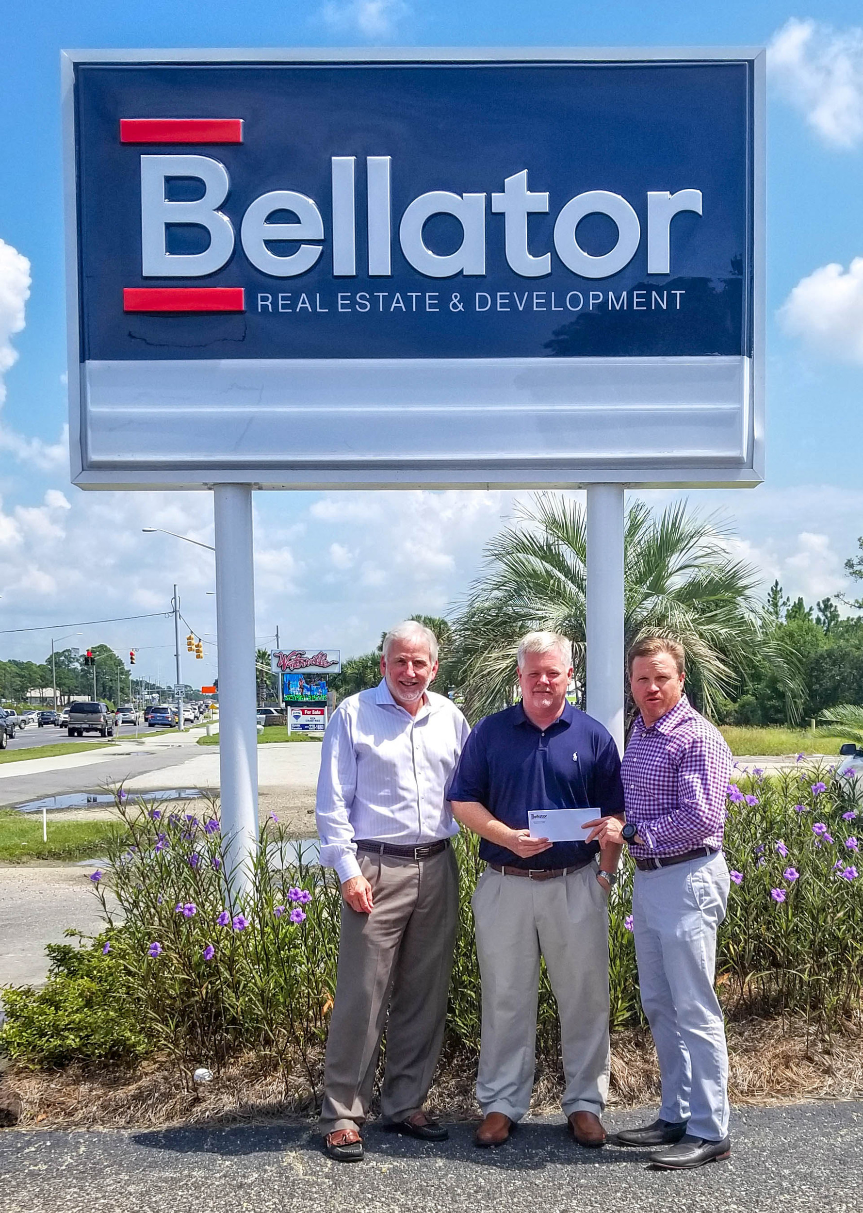 Bellator Real Estate & Development acquires Triple Option Properties: From left, Bellator Gulf Shores Managing Broker Frank Malone, REALTOR® Brad Chambers, formerly of Triple Option Properties, and Bellator President Troy Wilson stand in front of the Gulf Shore's office sign.