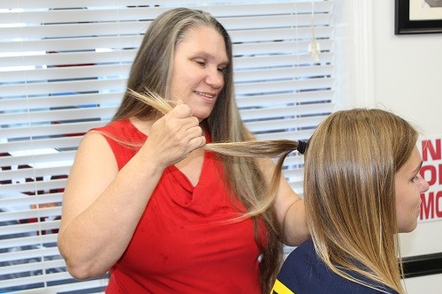 D.J. Payne's mother, Jacqueline, makes ponytails in preparation the cutting.