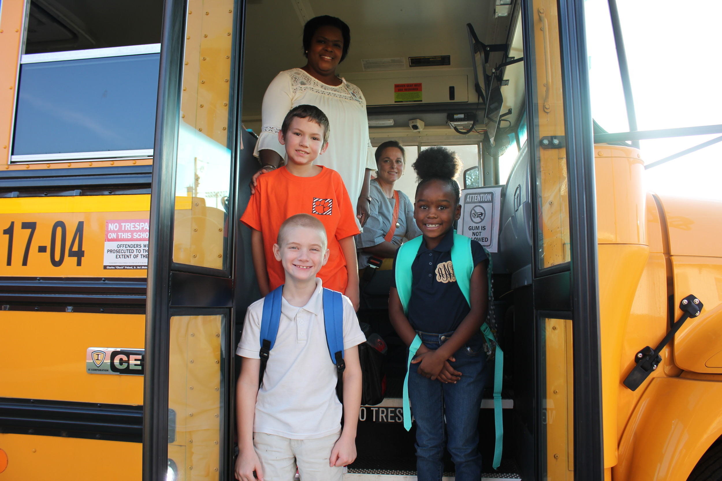 Assistant Principal Katina Smith-Davis welcomes students Nathan Walley, Nicholas Bledsoe, and Andriana Nelson arriving on Adrienne Boeschen's bus.