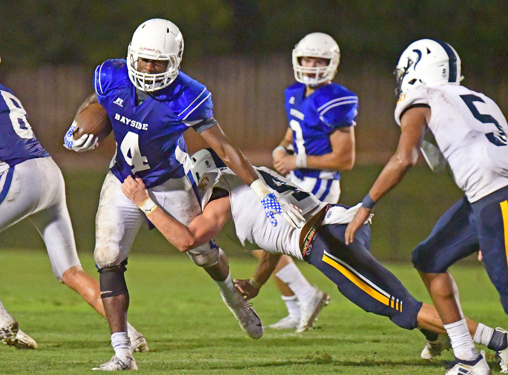 Nathan Cook (4) fends off a tackler for extra Bayside yardage at Freedom Field. The senior scored two touchdowns for the Admirals.