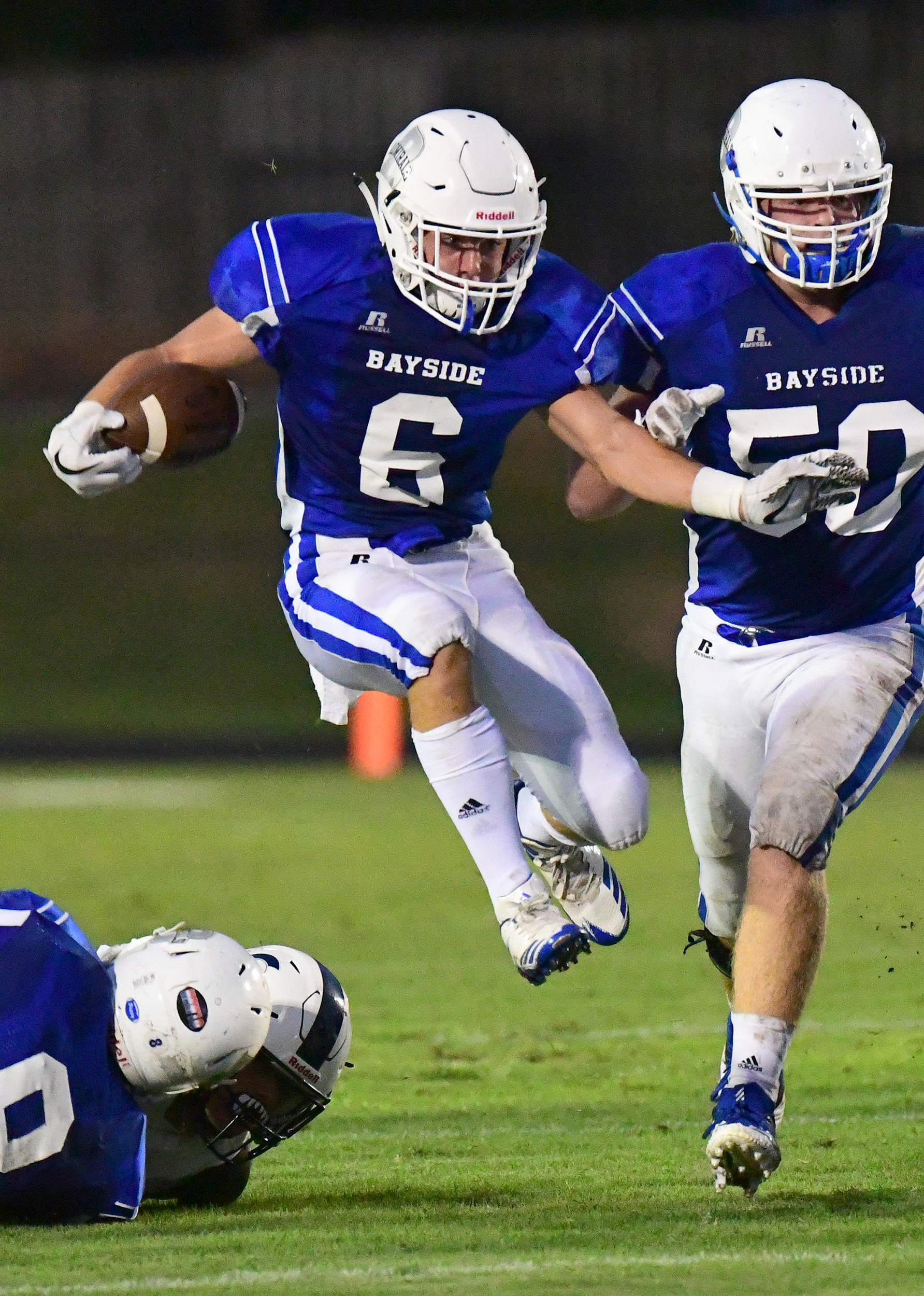 Senior convoy: Jacob Cunningham finds an opening with blocking from Austin White, left, and a downfield escort by senior Admiral James Cassity.