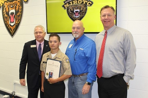 Robertsdale High School Naval Junior ROTC cadet Keanan Ard receives the Legion of Valor Bronze Cross for Achievement Award, surrounded by Baldwin County School Superintendent Eddie Tyler, Robertsdale Mayor Charles Murphy and RHS Principal Joe Sharp.