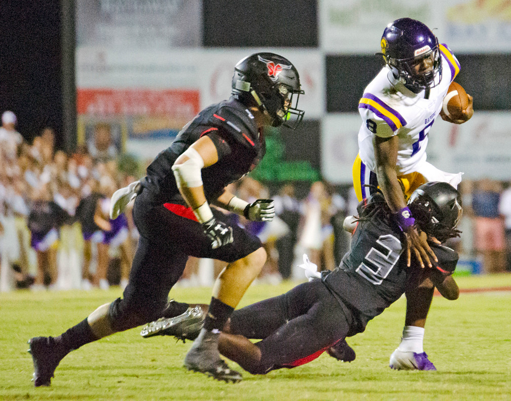 Michael Miller (3) makes a diving tackle for the Toros on Daphne quarterback Trent Battle.