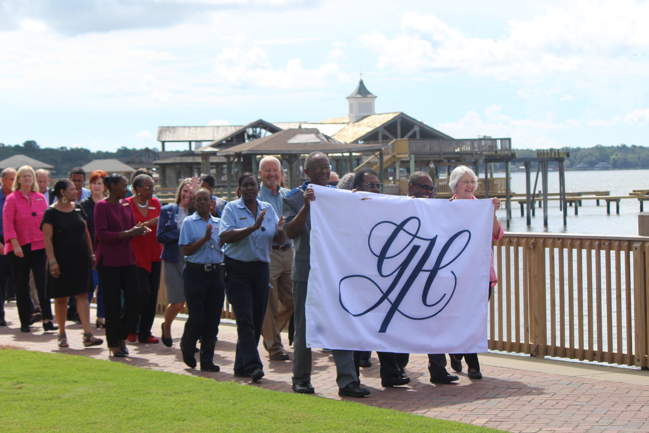 Legacy staff members of the Grand Hotel in Point Clear carry the new flag to be raised on site as a symbol of the hotel's completed renovations and new status as a Marriott Autograph Collection destination.