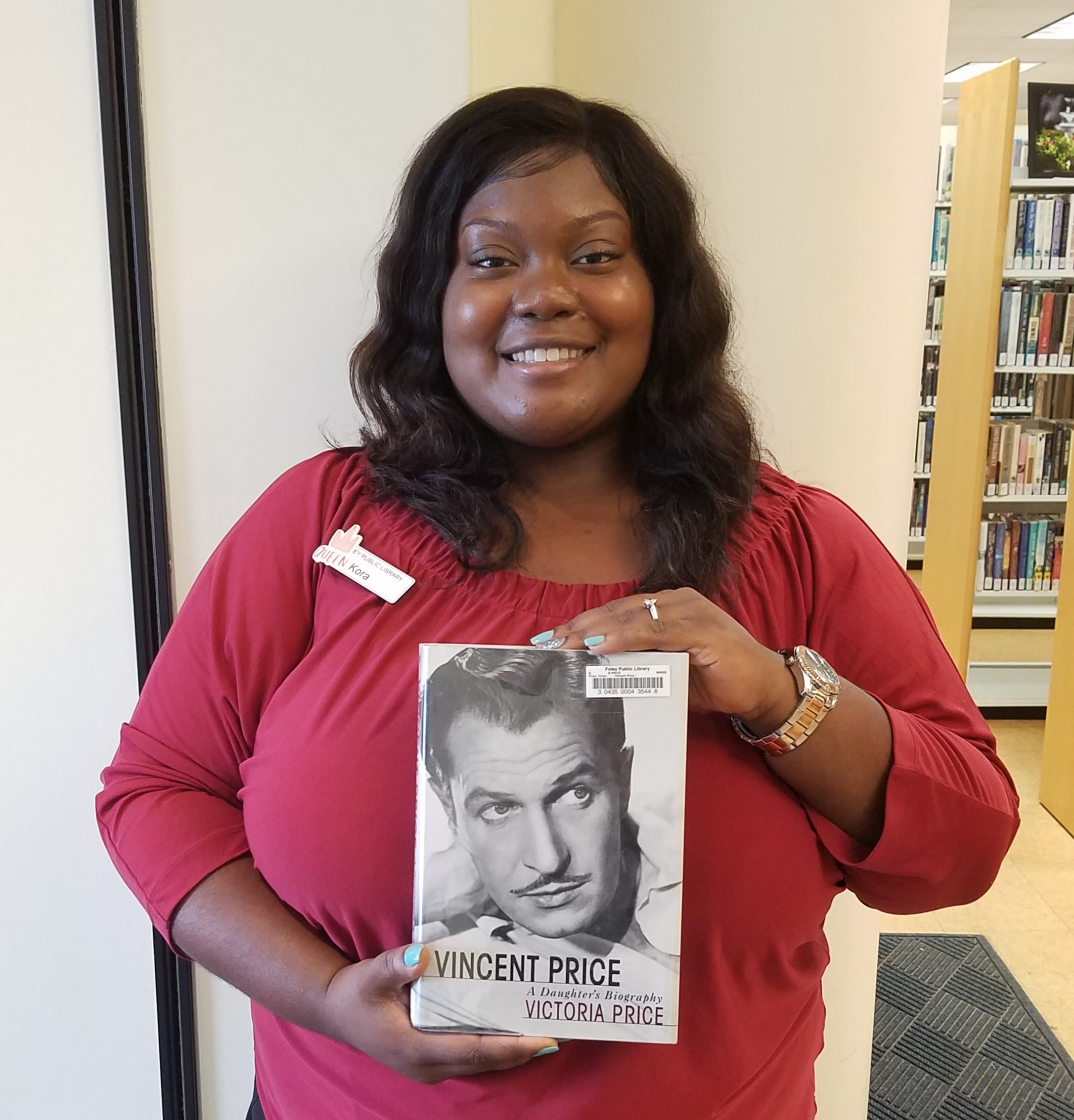 Library Aide, Kora Benford, holding a Vincent Price biography available at the Foley Public Library.