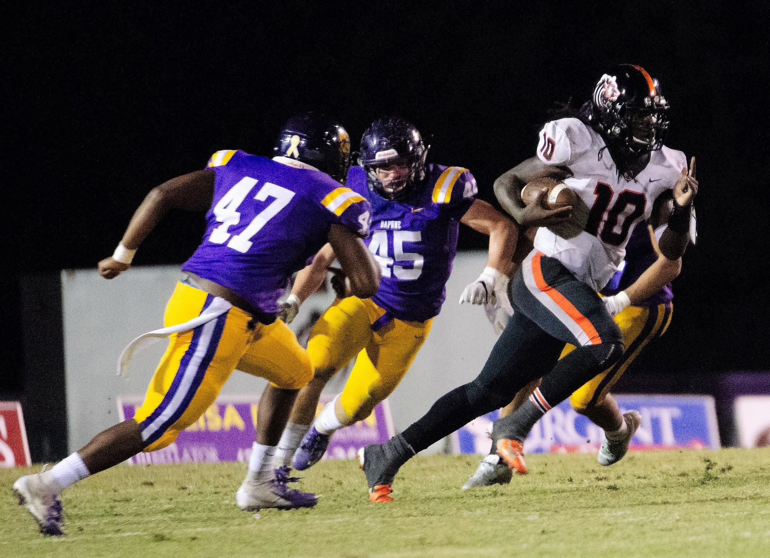 Anthony (A.J.) Mix (10) speeds through a gap between defenders Ricky Hankins (47) and Timothy Getch (45) at Daphne.