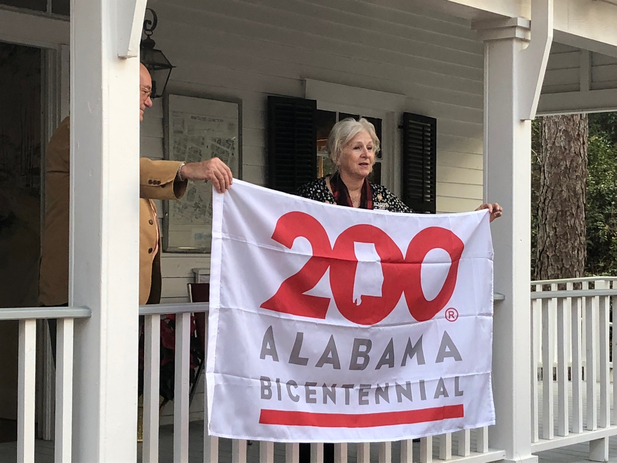 Former Baldwin County Historic Development Commission Chairwoman Claudia Campbell presents the Montrose community with a flag celebrating Alabama's bicentennial.