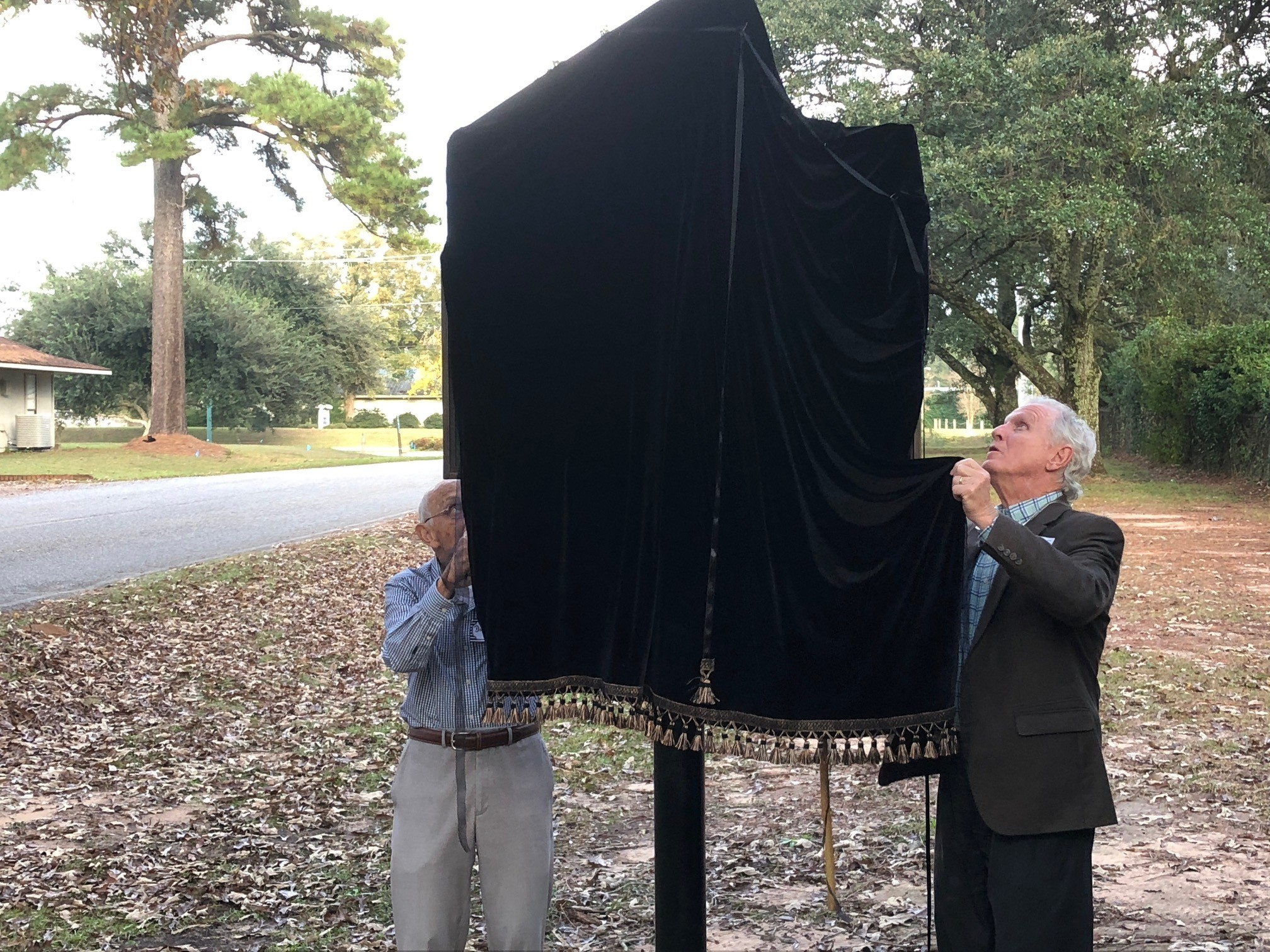 Montrose Cemetery Board trustees Dick Scott and Steve Moore help unveil the new historic marker for the Village on Montrose, located on Sibley Street outside the Montrose Cemetery.