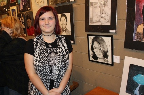 BriAnna Bettner, a student at Elberta High School, displays her art at Lyons Share Gallery in Fairhope as part of the First Friday Art Walk Jan. 4. Her art, a self-portrait in charcoal, along with artwork from students throughout Baldwin County will be on display throughout the month of January.