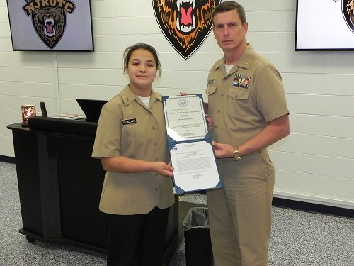 Cadet Seaman Apprentice Sierra Seladones receives the Meritorious Achievement Ribbon from Lt. Commander Frank Starr, senior Naval Junior ROTC instructor at Robertsdale High School.