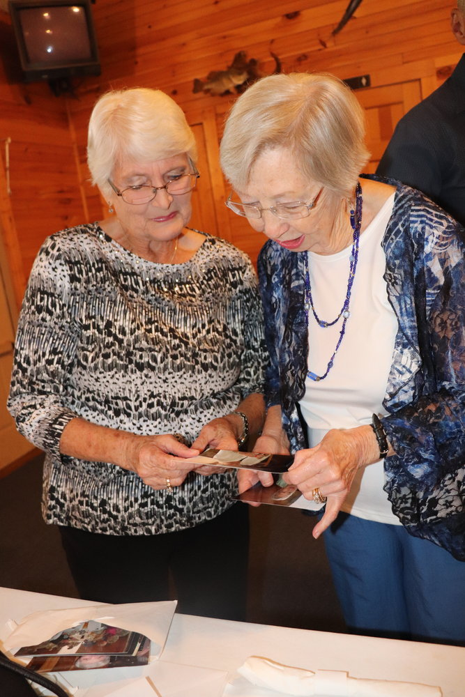 Classmates of the Fairhope High School class of 1954 look over old photos during their 65th reunion dinner Saturday.