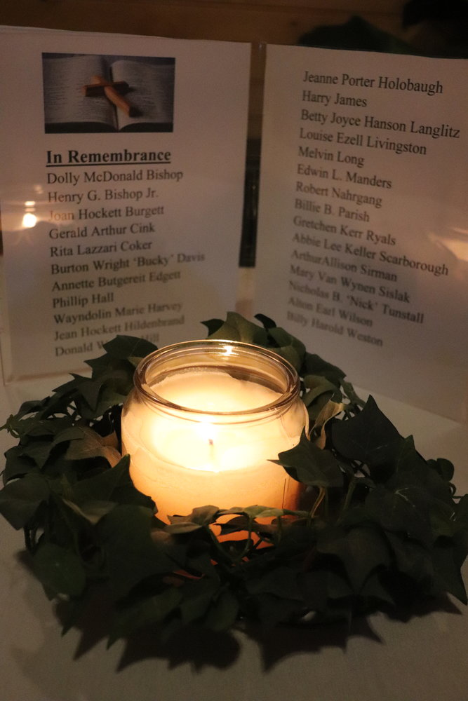 A candle illuminates the names of members of the class of 1954 who have passed away.