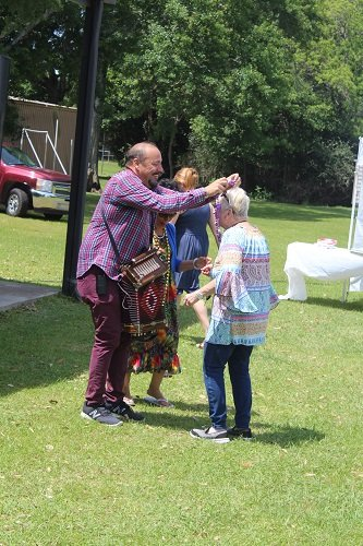 Terrance Simien hands out beads to participants.