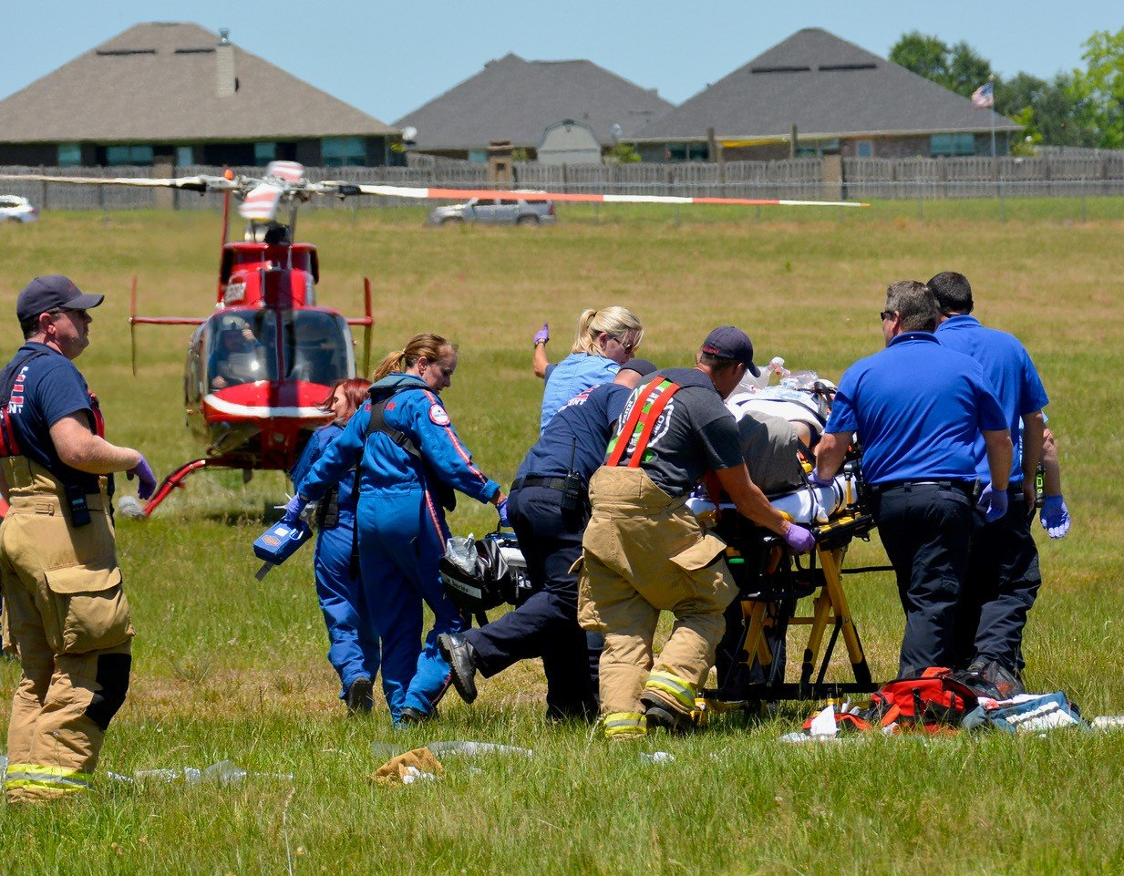 First responders take one of the injured pilots to a waiting MedStar helicopter.