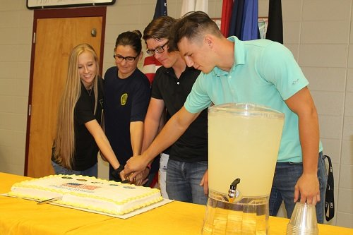 RHS students representing each branch of the military cut the cake using a ceremonial sword at a military signing day Thursday, May 9 at Robertsdale High School. Pictured, from left, are Olivia Dugger, representing the Army; Sara Lowrey, representing the Navy; Immanuel Taylor, representing the Air Force; Joshua Abbott, representing the Marine Corps; and Chance Coleman, representing the National Guard.