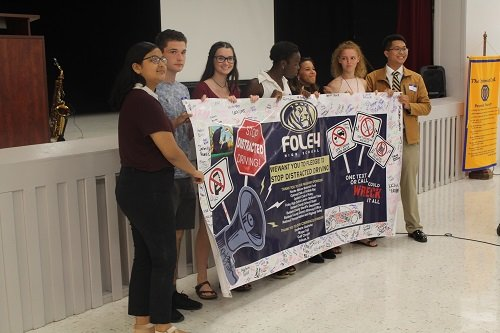 Members of the Foley High School Junior Optimist International club present a pledge to end distracted driving.