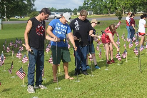 "Cadets from the Robertsdale High School Naval Junior ROTC place flags on Monday as part of ""Operation Patriot59"" set up to honor the 58,220 Americans who lost their lives in the Vietnam War."