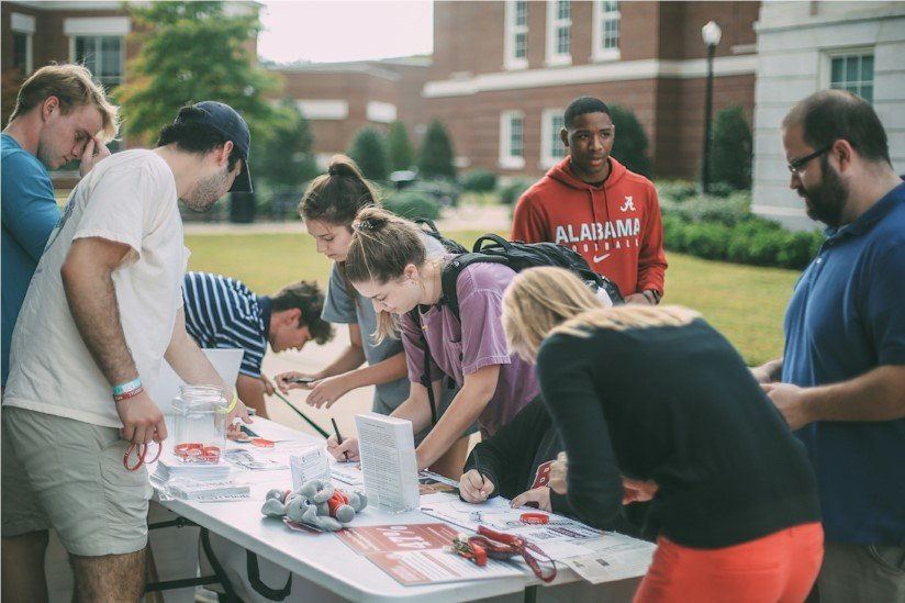 Students signing safe driving pledges at Hunter Watson Safe Driving Campaign event at University of Alabama.