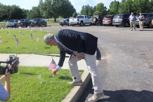 Glenn Sykora places a flag in honor of his brother Robert J. Sykora, honored as part of those who died during the Vietnam War following a ceremony to dedicate the Memorial Wall of Honor Thursday, May 23 at Robertsdale High School.
