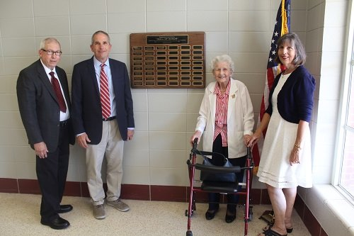 The Sykora family is pictured with the Robertsdale High School Memorial Wall of Honor, which currently includes 17 names, including Robert J. Sykora. A flag dedicated to Sykora is also on display in the lobby at the high school.
