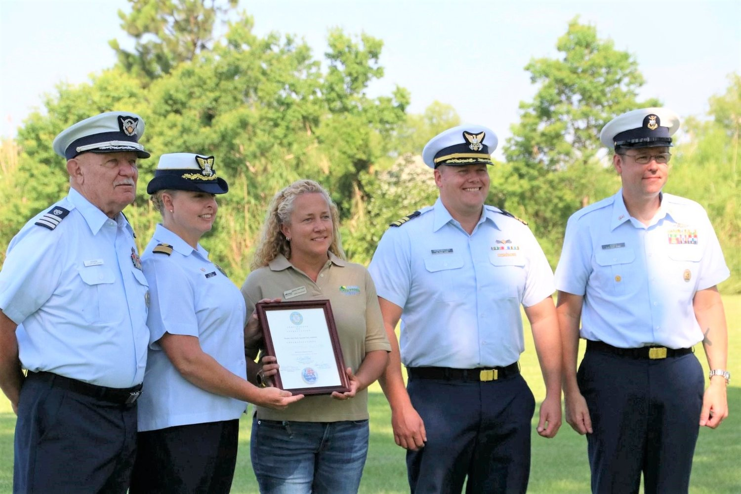 Sector Mobile Commanding Officer LaDonn Allen and other Coast Guard officers present Meaher State Park Superintendent Anna Bryant with a certificate of appreciation.
