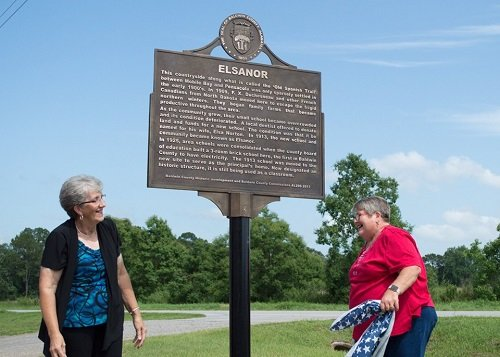 Brenda Wilsey Rabren and Barbara Beverly unveil the Baldwin County Historic Marker at the Elsanor Community Center on U.S. 90.
