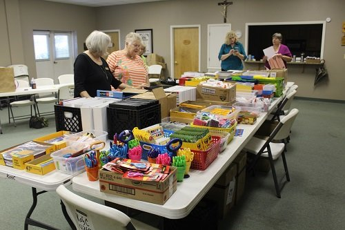 Baldwin County Catholic Social Services Director Phyllis Beam, left, Volunteer Coordinator Peggy Peterson, second from right, and volunteers fill backpacks for Project R.E.A.C.H. at the Knights of Columbus Hall in Robertsdale.