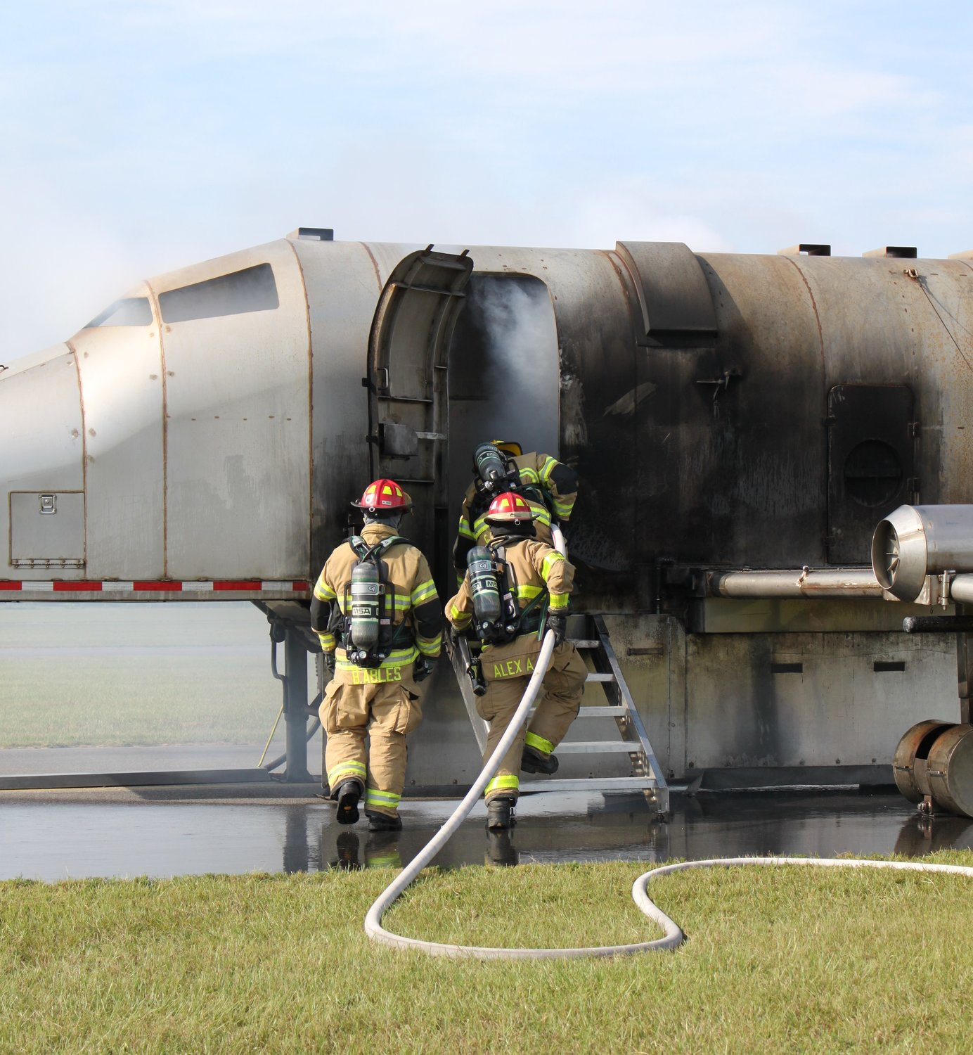 Fire crew moves into the fuselage to fight an interior fire.