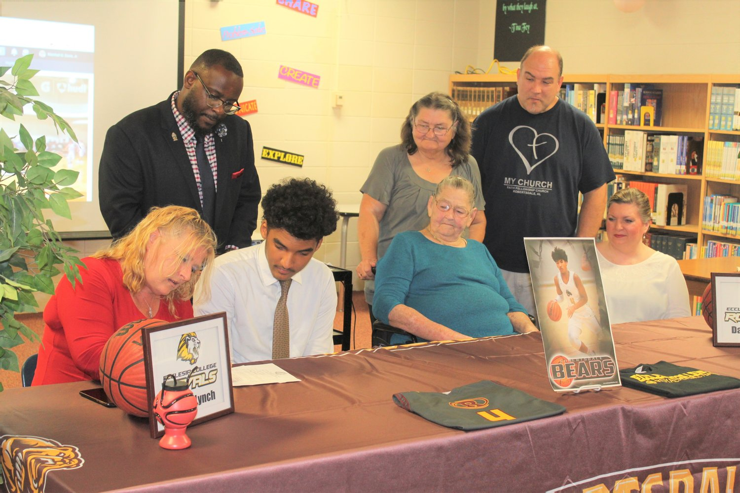 "Robertsdale High School alum David Lynch signs Wednesday, Aug. 7 with Ecclesia College as Coach Marshall Davis, standing, mom Stephanie Williams, left, great-grandmother Lana Wilson, grandmother Sara Weaver and ""adopted parents"" Mike and Tammie Kelso look on."