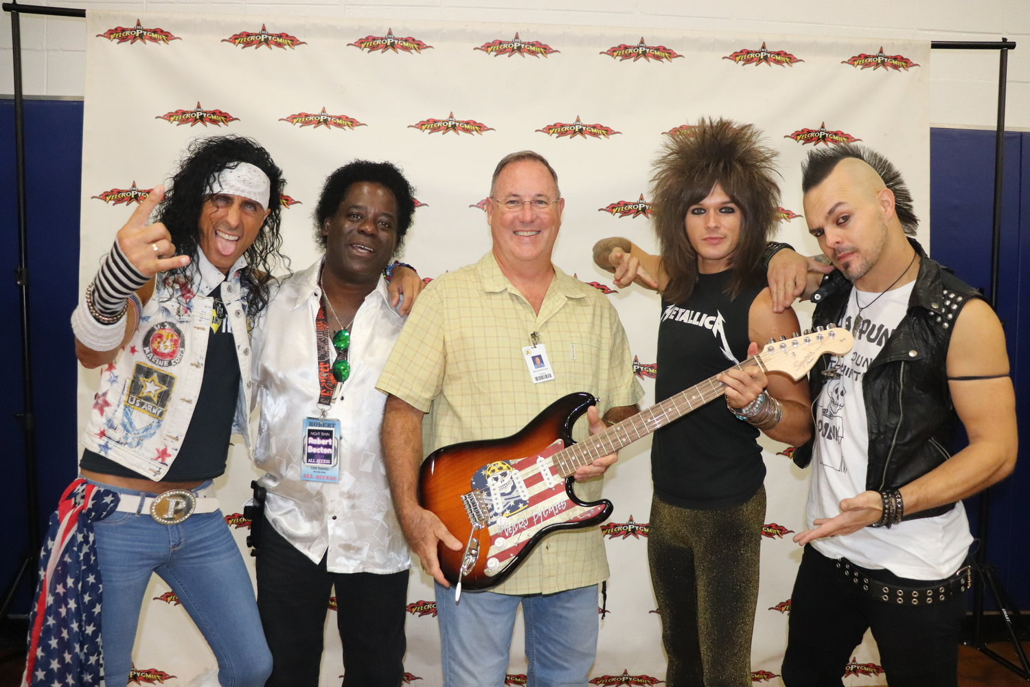 Michael McCrady, PiraGraphiX career tech instructor, poses with the custom guitar his student designed and members of the Velcro Pygmies.