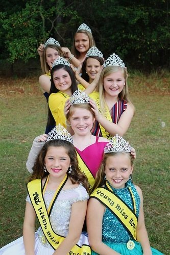 The six past Little Miss HoneyBee queens pass the crowns to this year's queens, Little Miss HoneyBee Caroline Taylor and Young Miss HoneyBee Portia Hollis.