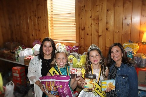 From left, President Stephanie Kroll, Young Miss HoneyBee Portia Hollis, Little Miss HoneyBee Caroline Taylor and Vice President Leslie Kyte pictured in front of 4,000 food donations.