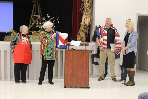 Phyllis Beam with the Stitch-n-Friends group present Robert Scott Loxley and his wife Robyn with Quilts of Valor.