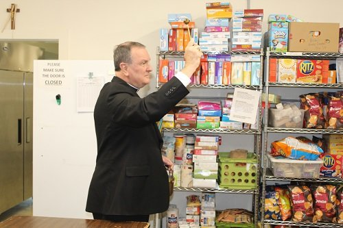Archbishop Thomas Rodi blesses the Catholic Social Services food pantry.