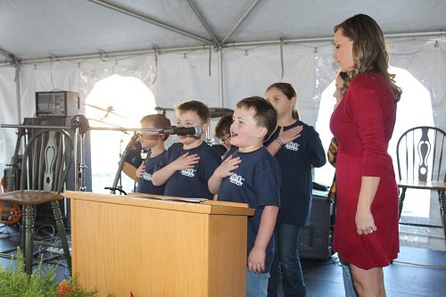 Tiffany Driver and Rosinton School students lead the Pledge of Allegiance.