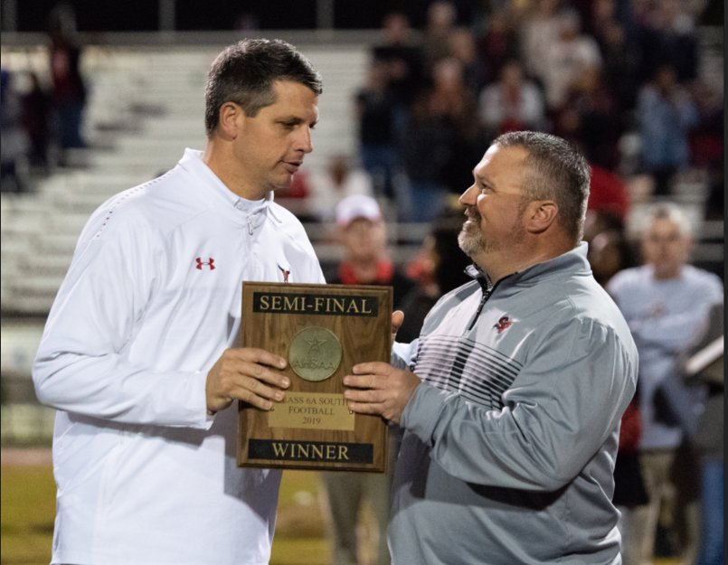 Toros coach Ben Blackmon (left) receives the AHSAA South Region Semi-Finals Winner Award from Spanish Fort High principal Brian Williamson.