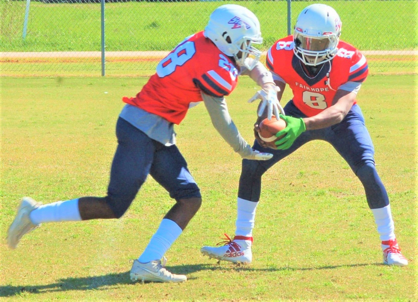 Storm quarterback Quincy Durgin hands off to former Fairhope running back C.J. Edwards.