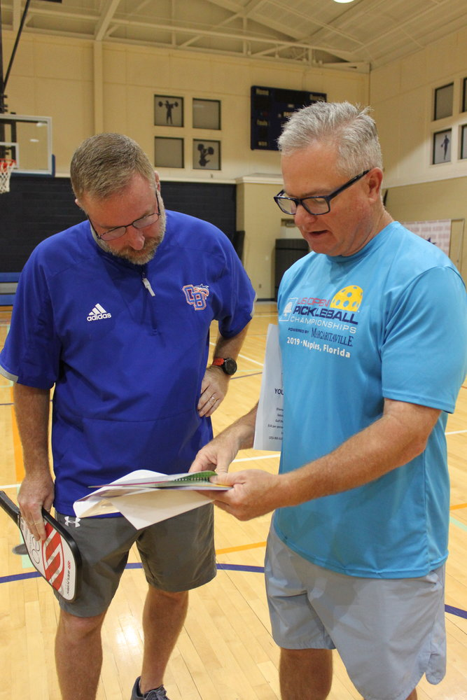 Shane Alexander and Eddie McDonald go over the educational posters and handbook for the pickleball equipment the Bama Beach Pickleball Club donated to Orange Beach Middle School.