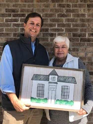 Mayor Jared Lyles presents February winner Diane Lores with her prize.