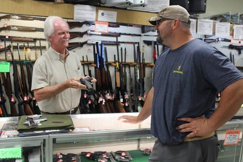 Nelson Wingo, owner of Campbell's Hardware & Sporting Goods in Robertsdale, talks guns with customer Clay Blankenship.