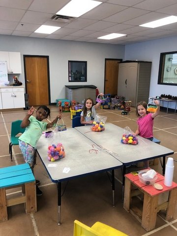 Making Easter baskets with bags of eggs given to the Y by OWA.